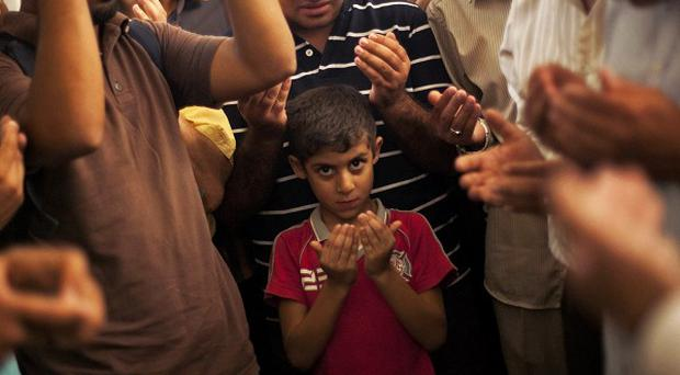 A son of the late Ammar Badie prays during his father's funeral in al-Hamed mosque in Cairo's Katameya district (AP)