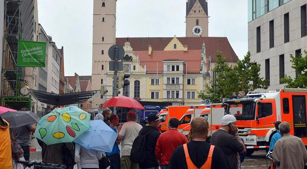 Onlookers in front of the city hall in Ingolstadt where a gunman has taken hostages (AP)
