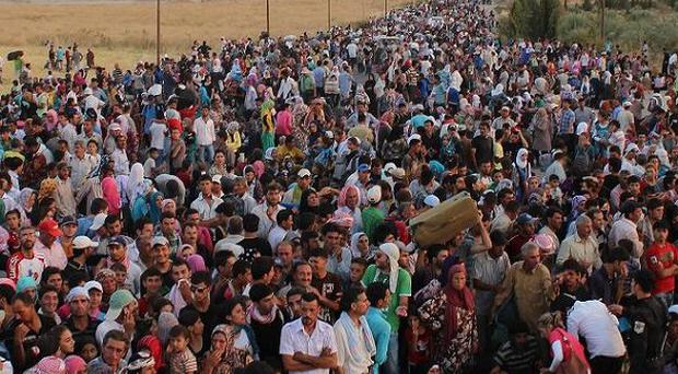 Syrian refugees pour over the border into Iraq (AP)