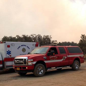 Fire and medical personnel stand by as smoke fills the skies (AP)