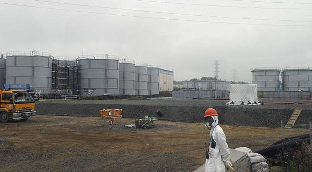 A construction worker walks beside the underground water tanks at the Fukushima Dai-ichi nuclear plant (AP)