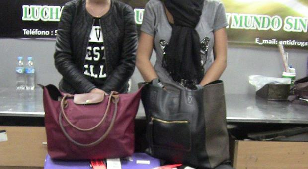 Michaella McCollum, left, and Melissa Reid stand behind their luggage after being detained at the airport in Lima, Peru (AP)