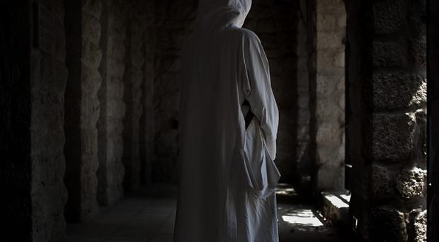 A nun looks at damages at the Beit Gemal monastery (AP)