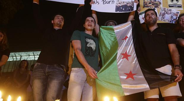 Syrian citizens who live in Beirut, hold a revolutionary flag and placard that reads: