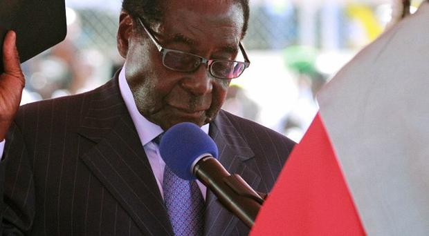 Zimbabwean President Robert Mugabe holds the bible during his inauguration in Harare (AP)