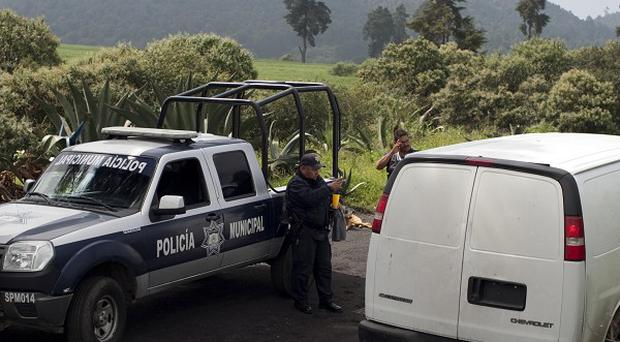 Vans belonging to Mexican authorities arrive at the entrance of a ranch where a mass grave was found in Tlalmanalco (AP)