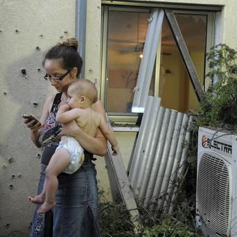 An Israeli woman holds her child outside her home damaged by a rocket fired from Lebanon in Shavei Tzion outside Nahariya in northern Israel (AP)