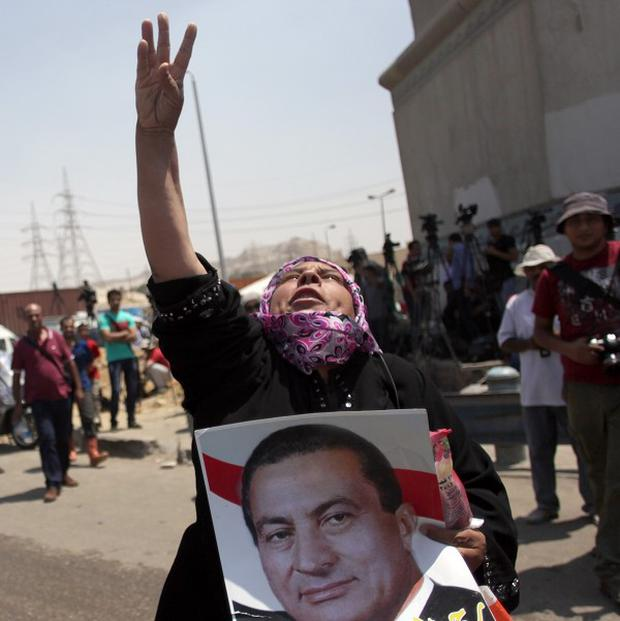 A supporter of Hosni Mubarak holds a poster of him and chants slogans before his release from jail (AP)