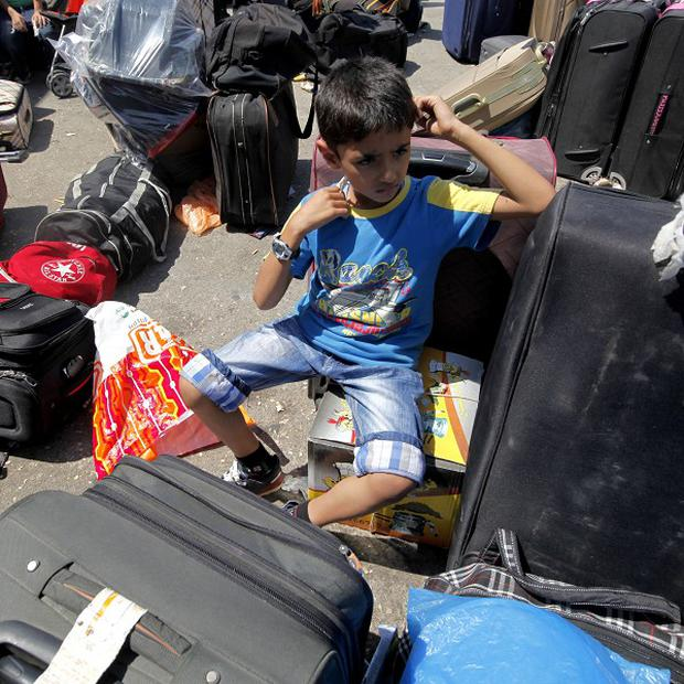 A Palestinian child sits with his family's luggage at the border between the Gaza Strip and Egypt (AP)