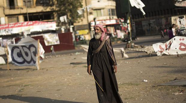 A man walks through Tahrir Square where a few protesters have built their camp protesting against the release of Hosni Mubarak in Cairo, Egypt (AP)
