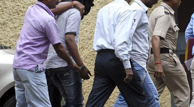 Police officials escort an accused, head covered with black cloth, in the gang rape of a young photojournalist in Mumbai (AP)