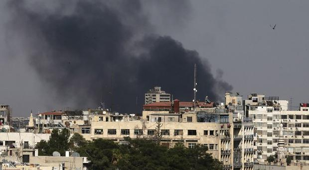 Black columns of smoke rise after heavy shelling in the Jobar neighborhood, east of Damascus in Syria (AP)