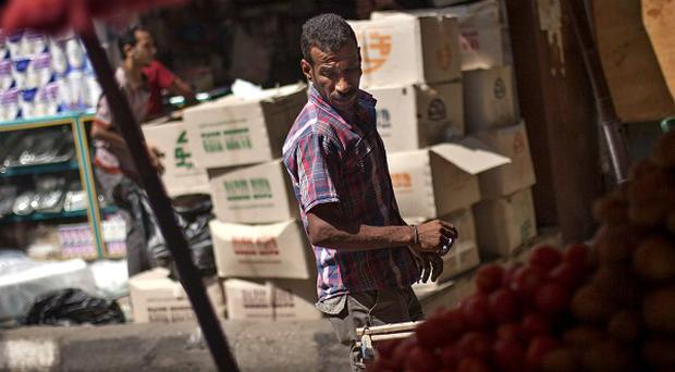 A fruit seller waits for customers in Cairo; Egypt's recent turmoil has scared away tourists (AP)