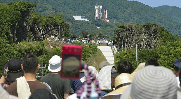Spectators watch the Epsilon rocket on its launch pad after its countdown at the Uchinoura Space Centre in Kimotsuki, Kagoshima (AP/Kyodo News)