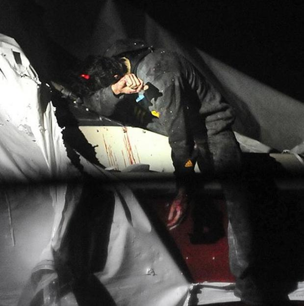 Boston Marathon bombing suspect Dzhokhar Tsarnaev leans over in a boat at the time of his capture (AP/Massachusetts State Police, Sean Murphy)