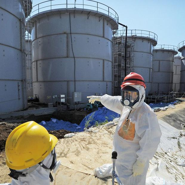 Japanese trade minister Toshimitsu Motegi inspects storage tanks at the Fukushima Dai-ichi nuclear plant (AP/Kyodo News)