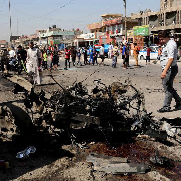 People inspect the site of a car bomb attack in Sadr City, Baghdad (AP)