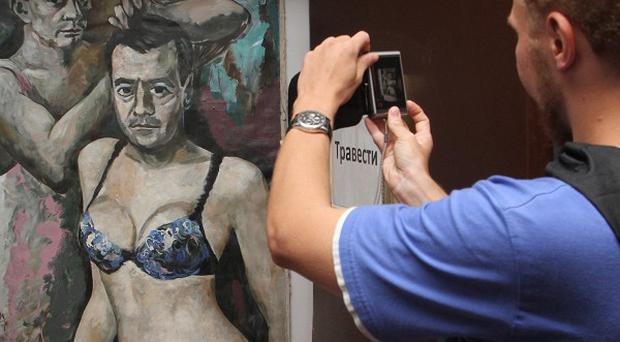 A gallery visitor takes his own picture of the painting (AP)
