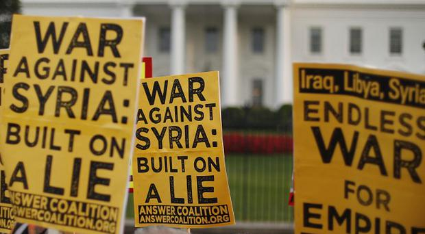 Demonstrators take part in a protest calling for no military attack against Syria outside the White House in Washington (AP)