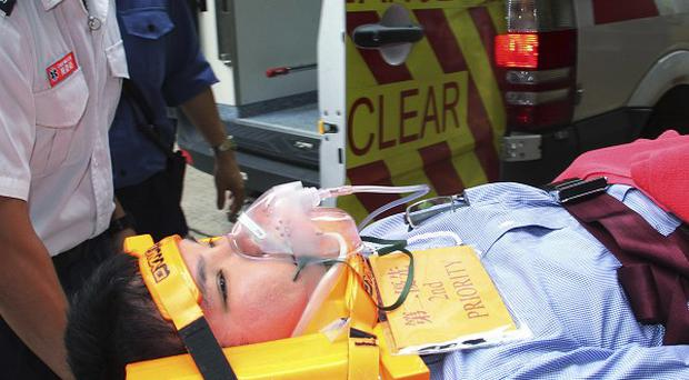 An injured passenger of Thai Airways is carried to a hospital in Hong Kong (AP)