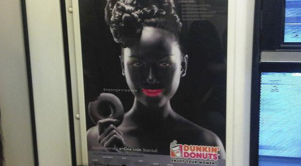 A racism row broke out over this advertisement showing a smiling woman with bright pink lips in black face makeup holding a doughnut (AP)