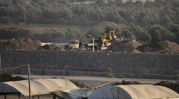A bulldozer looks over smuggling tunnels along the border with Egypt as seen from Rafah, southern Gaza Strip (AP)