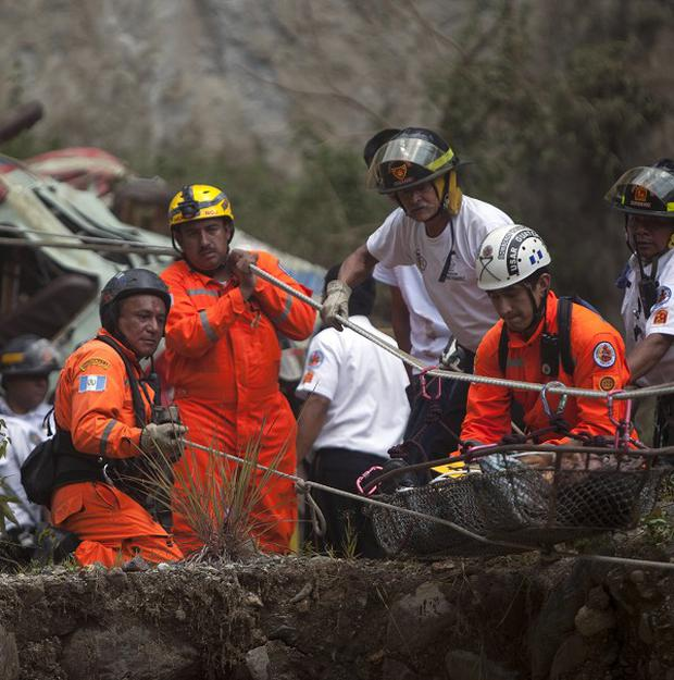 Rescuers remove the body of a passenger after a bus plunged into a river canyon in San Martin Jilotepeque, Guatemala (AP/Luis Soto)