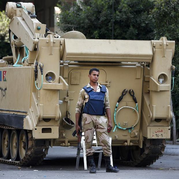A soldier stands guard next to an armoured personnel carrier in Cairo, Egypt (AP/Lefteris Pitarakis)