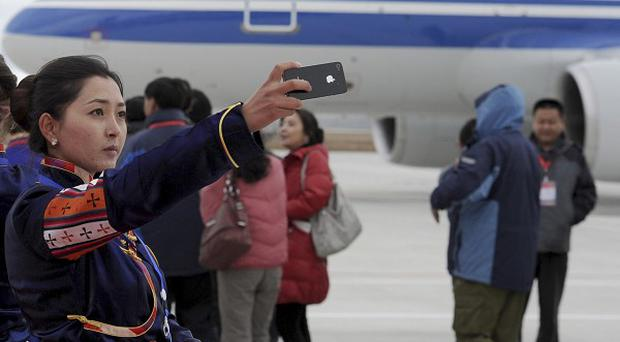 A Tibetan woman uses her phone to take photos of a flight that touched down at Yading airport, the world's highest-altitude civilian airport (AP)