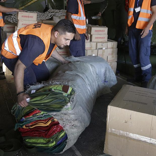 A Lebanese airport worker unloads aid supplies in Beirut which will be given to Syrian refugees in the country (AP)