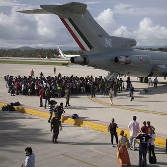 Hundreds of stranded tourists gather around a Mexican Air Force jet as they wait to be evacuated at the air base in Pie de la Cuesta near Acapulco, Mexico (AP)
