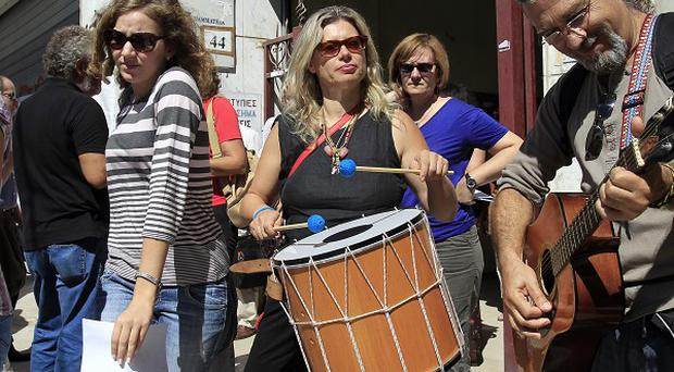 Striking school teachers play music during a protest against job cuts in the northern port city of Thessaloniki (AP)