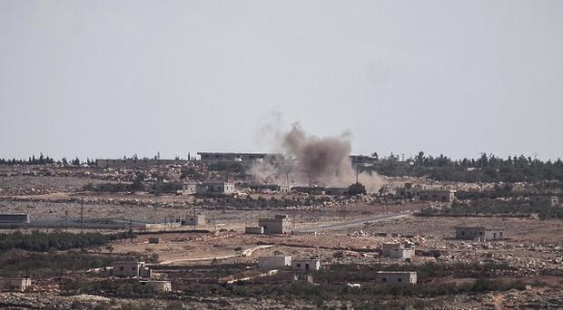 Smoke rises as a mortar shell hits a rebel position in the Idlib Provence countryside of Syria (AP)