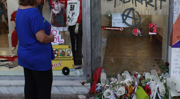 A woman stands in front of the site where Pavlos Fyssas died near Athens (AP)