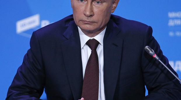 Vladimir Putin says a new law that has drawn protests worldwide does not infringe on the rights of gay people (AP)