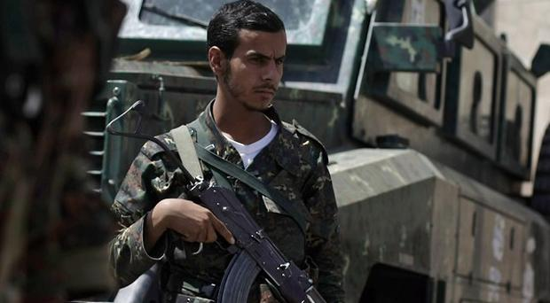 Yemeni soldiers man a checkpoint following attacks by al-Qaida militants (AP)