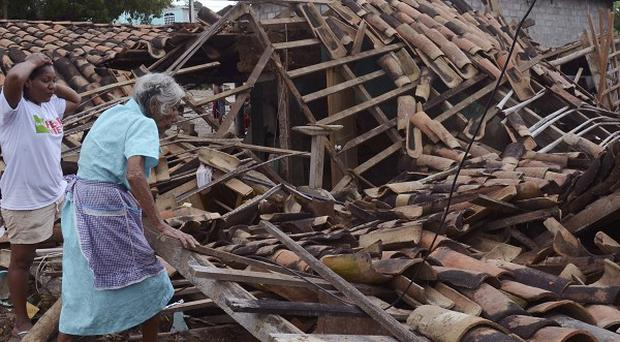 Two women try to salvage what was left of their home after it was destroyed by the rains and floods (AP)