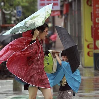 A woman and her child hold their umbrellas tight against powerful gusts of wind as typhoon Usagi approaches in Taipei (AP)