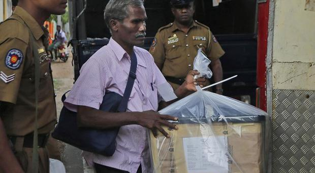 A Sri Lankan election officer loads a sealed ballot box into a bus at the end of voting in Jaffna (AP)