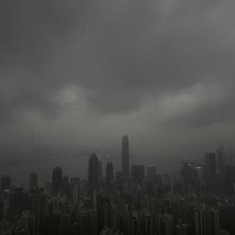 Dark clouds hang low over Hong Kong's Victoria Habour as the year's most powerful typhoon approaches (AP)