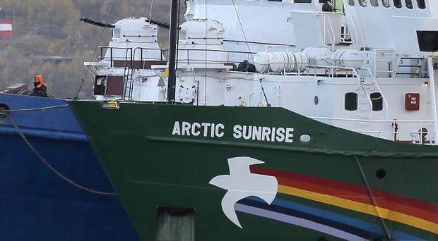 The Greenpeace ship is escorted into harbour by a Russian coast guard ship (AP)
