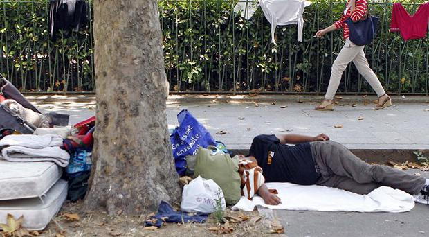 A Roma immigrant resting near the Bastille in Paris (AP)