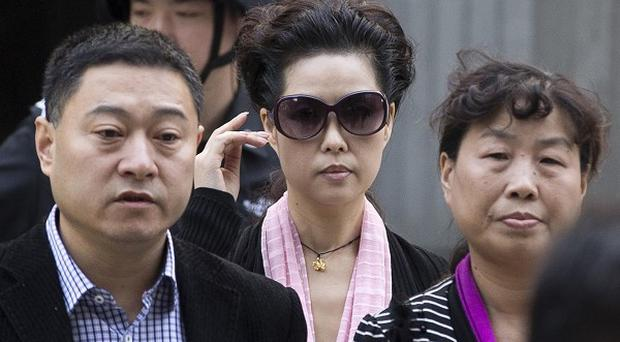 Celebrity singer Meng Ge, the mother of Li Tianyi, adjusts her sunglasses as she leaves the Haidian District People's Court (AP)
