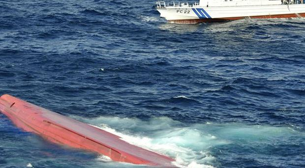 A capsized Japanese freighter is seen as a Japan Coast Guard patrol boat conducts a search operation for missing crew members (AP/Kyodo News)