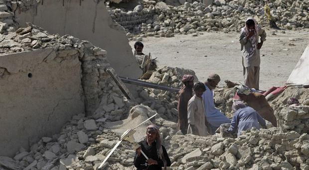Pakistani men collect useful items from rubble of houses, which were destroyed in Tuesday's earthquake, in the remote district of Awaran in Baluchistan province, Pakistan.