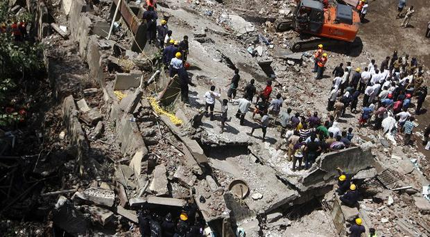Rescue workers look for survivors and clear debris at the site of a building that collapsed in Mumbai, India (AP)