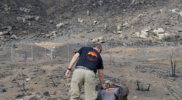 Prescott wildland division chief Darrell Willis touches a Granite Mountain Hotshots crew shirt draped over a burned cactus in Yarnell, Arizona (AP)