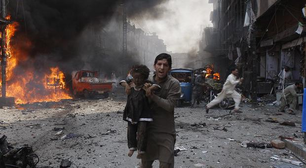 A man carrying a child rushes away shortly after a car exploded in Peshawar, Pakistan (AP)