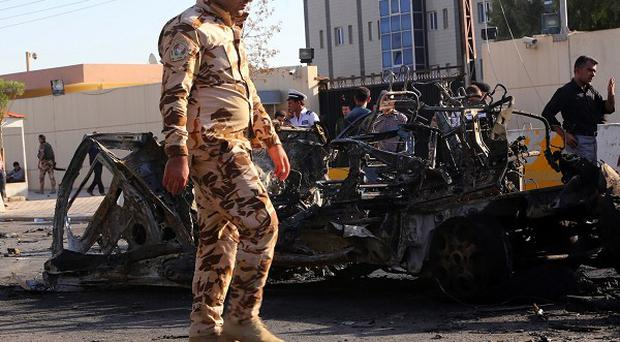 Security forces and citizens inspect the site of a car bomb attack in Irbil. (AP)
