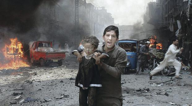 A man carries a child away from the blast scene shortly after a car bomb exploded in Peshawar, Pakistan
